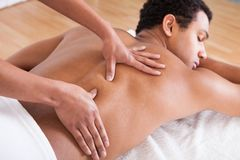 Man receiving massage from female hand Stock Image