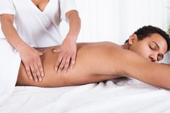 Man receiving massage from female hand Stock Images