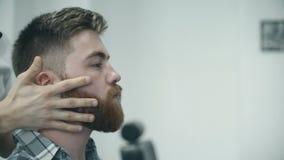 Man receiving massage on his beard stock video