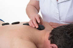 Man receiving a massage with hot stone in a health spa Stock Photography