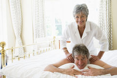 Man receiving a massage from a woman. In the bedroom stock images