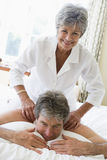 Man receiving a massage from a woman. In the bedroom stock photo