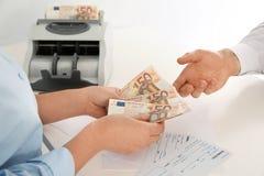 Man receiving money from teller at cash department. Closeup stock photography
