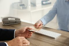 Man receiving money from teller. At cash department window, closeup royalty free stock photo