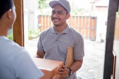 Package delivery box. Man receiving a package at home from a delivery guy Royalty Free Stock Photography