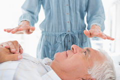 Man receiving Reiki treatment by therapist Stock Images