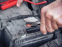 Man recharging a dead car battery in winter time using start-charger. Close up hands of a man with two contact clips royalty free stock images