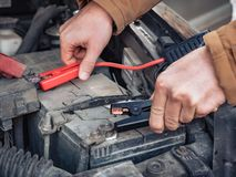 Man recharging a dead car battery in winter time using start-charger. Close up hands of a man with two contact clips royalty free stock image
