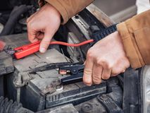 Man recharging a dead car battery in winter time using start-charger. Close up hands of a man with two contact clips stock photography