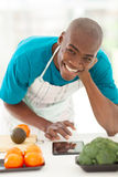 Man recipe tablet. Cheerful afro american man in kitchen searching recipe on tablet computer Royalty Free Stock Photo