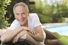 Man Reclining On Deck Chair In Garden stock images