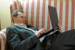 Man reclining with laptop Royalty Free Stock Photography