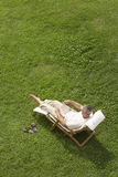 Man Reclining On Lawn In Deck Chair Reading Book Royalty Free Stock Photos