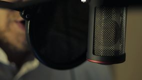 The man records his voice in the recording studio