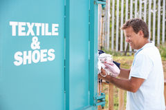 Man At Recycling Centre Disposing Of Clothing Royalty Free Stock Images