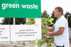 Man At Recycling Centre Disposing Of Garden Waste Stock Photos