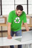 Man in recycling symbol tshirt working on laptop Stock Image