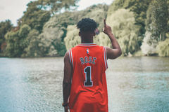 Man in Red #1 Basketball Jersey Pointing Up Standing in Front of River at Daytime Royalty Free Stock Photos