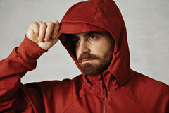 Man in a red anorak. Close up of a man with beard adjusting the hood of his red anorak isolated on white stock image