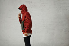 Man in a red anorak. A serious looking young man zips up his fashionable red and grey anorak, shot from the side isolated on white stock image