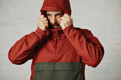 Man in a red anorak. Young bearded man covering his face with the hood of his brick red and dark grey anorak on white background royalty free stock photos