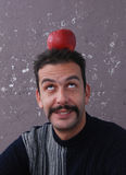 Man with red apple on a head. Picure of a man with red apple on a head Stock Photo