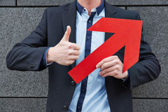 Man with red arrow holding thumbs. Man with red arrow leaning on wall and holding thumbs up Stock Image