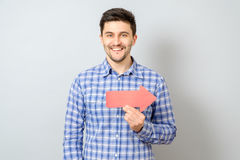 Man with red arrow pointing to the right. Isolated on gray Stock Photography