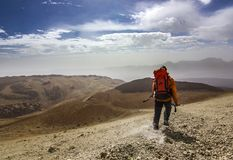 Man with red backpack on rocky path in desert. Man with backpack on path in desert near neide volcano on tenerife island with stones and blue sky and clouds Stock Photo
