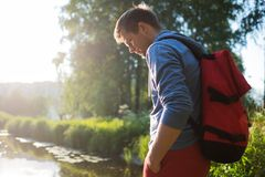 Man with red backpack walking in forest near river alone. Concept of having nice day outdoor in summer Stock Image