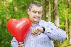 Man with red balloon. Staring at the clock Stock Images