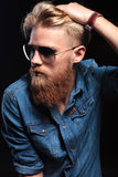 Man with red beard fixing his hair and looking away Royalty Free Stock Images