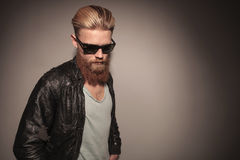 Man with red beard looking down. Picture of a cool guy with long red beard in leather jacket, looking down, on gray studio background stock photo