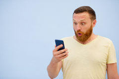 Man with a red beard looks into the phone with surprise and ecstasy a bright summer photo on a blue background Royalty Free Stock Photography