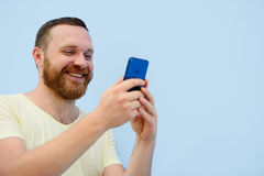 Man with a red beard looks into the phone with surprise and ecstasy a bright summer photo on a blue background Stock Photos