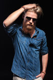 Man with red beard and sunglasses fixing his hair. Royalty Free Stock Photography