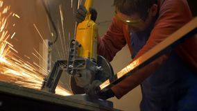 A man in a red and blue overall works with a circular saw. stock footage