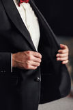 Man with red bow tie buttons up his black blazer Royalty Free Stock Photography