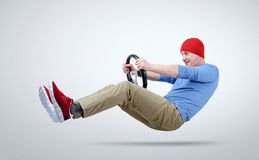 Man in red cap drives a car with a steering wheel Royalty Free Stock Photos