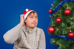 The man in a red cap scratches a nape sitting near a green fir-tree. Stock Image