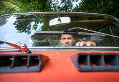 Man in a red car. White, middle aged man in a red, old russian car. Close up in front of the car Stock Image