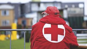 Man in red cross jacket Stock Image