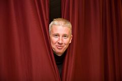 Man with red curtains Royalty Free Stock Images