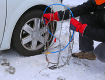 Man with red gloves install snow chains Stock Image