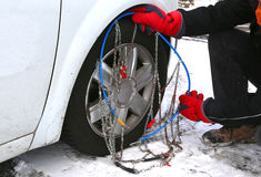 Man with red gloves install snow chains in the car tyre Royalty Free Stock Images