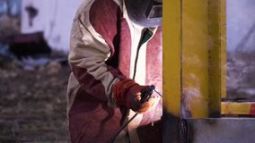 Man in red and gray robe welding yellow metal construction in safety gloves and safety mask. Safety first. Man in red and gray robe welding yellow metal stock video footage