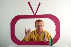 A man with red hair, a beard and a mustache in a yellow shirt, glasses parody the president`s speech on television. Christmas, Ne. W Year, holidays Stock Image