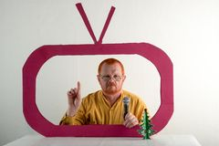 A man with red hair, a beard and a mustache in a yellow shirt, glasses parody the president`s speech on television. Christmas, Ne. W Year, holidays Royalty Free Stock Images