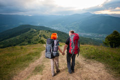 Man and red-haired woman on the road in the mountains Royalty Free Stock Photos