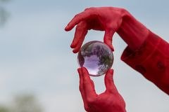 Crimson demon plays with crystal ball Royalty Free Stock Photography